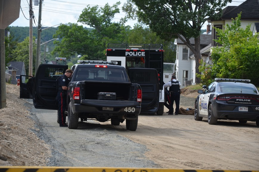 Police officers assess the scene on Queen Street in Miramichi Friday evening.