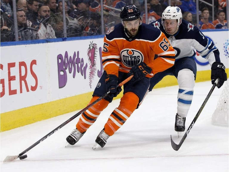 Edmonton Oilers forward Cooper Marody battles the Winnipeg Jets defenceman Tucker Poolman during pre-season NHL action at Rogers Place in Edmonton on Sept. 20, 2018.