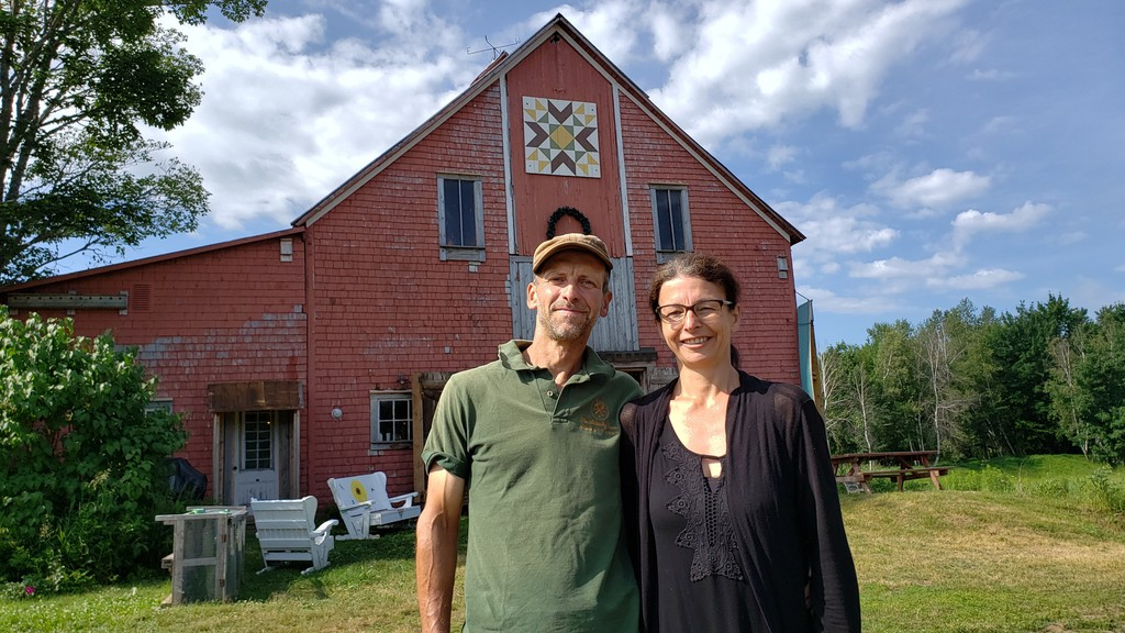 Stephan and Miriam Lobinsky in front of the red barn that houses the Burton Farmers and Artisan Market on their farm in Burton.