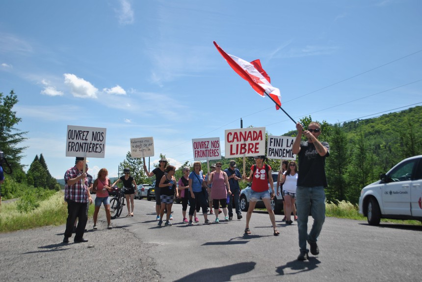 "Protester André Nadeau holds an upside-down Canadian flag during a protest against interprovincial border restrictions at the border of Quebec and New Brunswick near Edmundston, on July 4. ""I love my country, but right now I don't feel like I'm in my country,"" he said."
