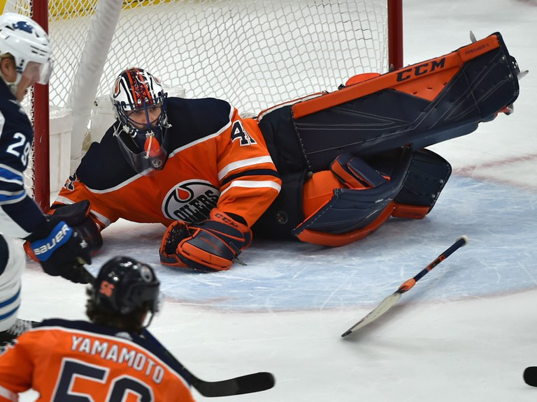 Edmonton Oilers goalie Mike Smith (41) dives across the cease and loses his stick after being caught out of position against the Winnipeg Jets at Rogers Place on March 11, 2020.