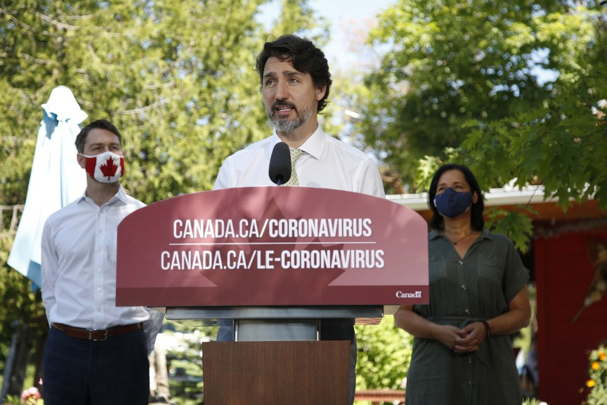 Justin Trudeau, Canada's prime minister, speaks during a news conference while cafe owner Manuela Teixeira, right, and Will Amos, a member of parliament, left, listen in Chelsea, Quebec, Canada, on June 19, 2020.