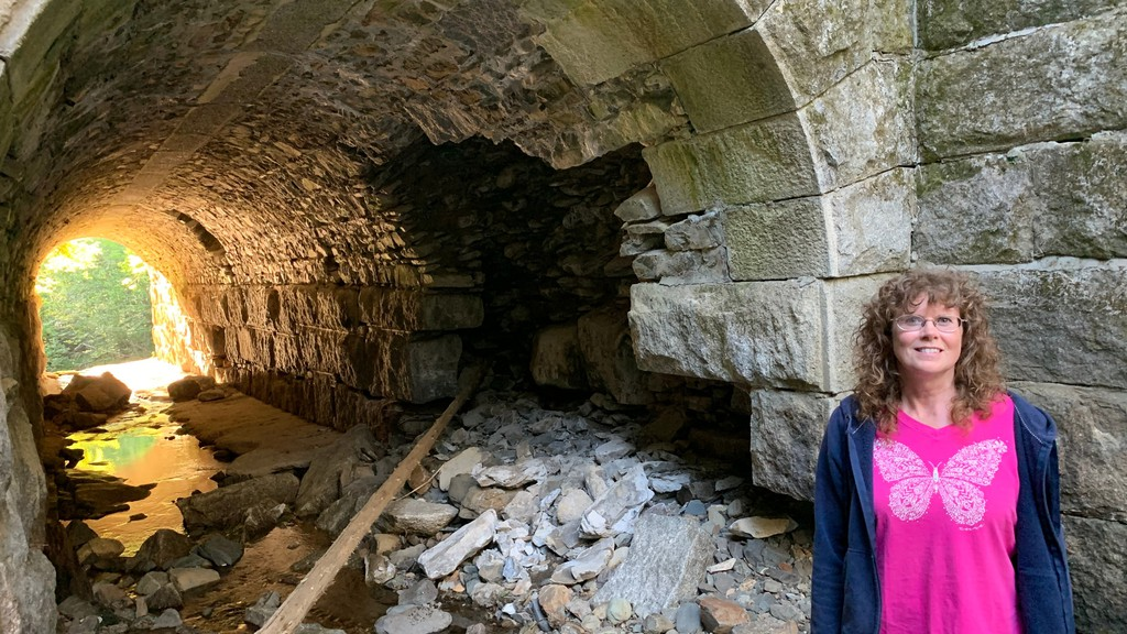 Shirley Sewell-McKell stands next to the deteriorating railway arch that allows the Shaw Brook to flow under the NB Sentier Trail. The brook is a short hike from the Newburg Road.