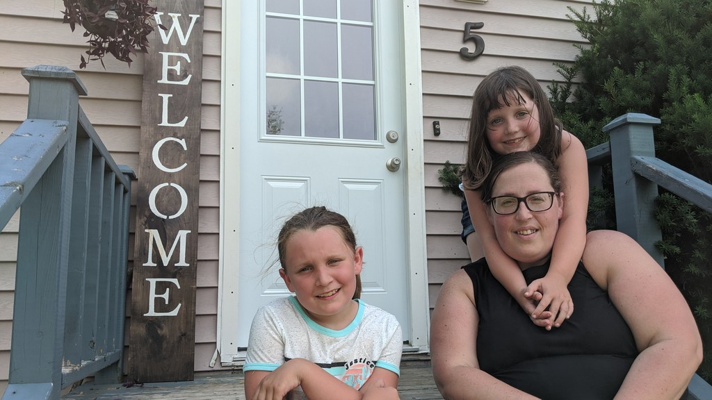 Pam Thomas sits with her daughters Teagan and Payton (standing) in front of their Moncton home. Thomas said driving her kids to and from school everyday is not an option.