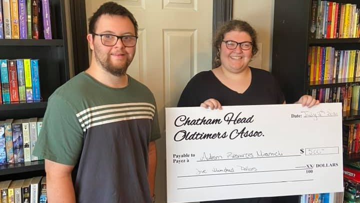 Andrew Sullivan presents the Chatham Head Oldtimers donation to Autism Resources Miramichi employee Emily O'Neill. The non-profit organization was one of several local groups that received a donation after the cancellation of the oldtimers' annual Chatham Head Days tournament.