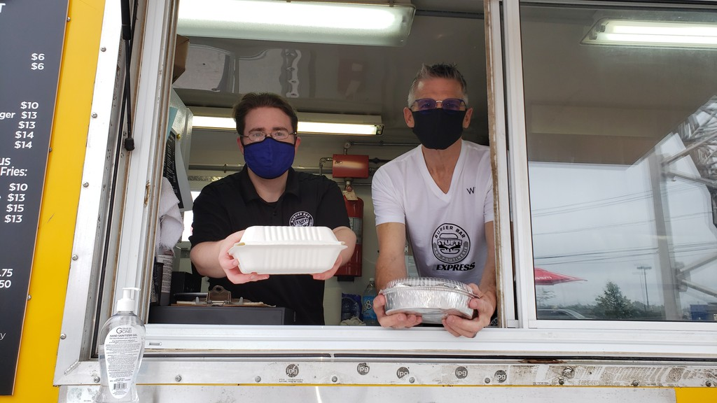 Server Nick Fitzpatrick, left, and manager Will Priest opened a new food truck to customers on Thursday at Stuft Burger Bar and Poutinerie.