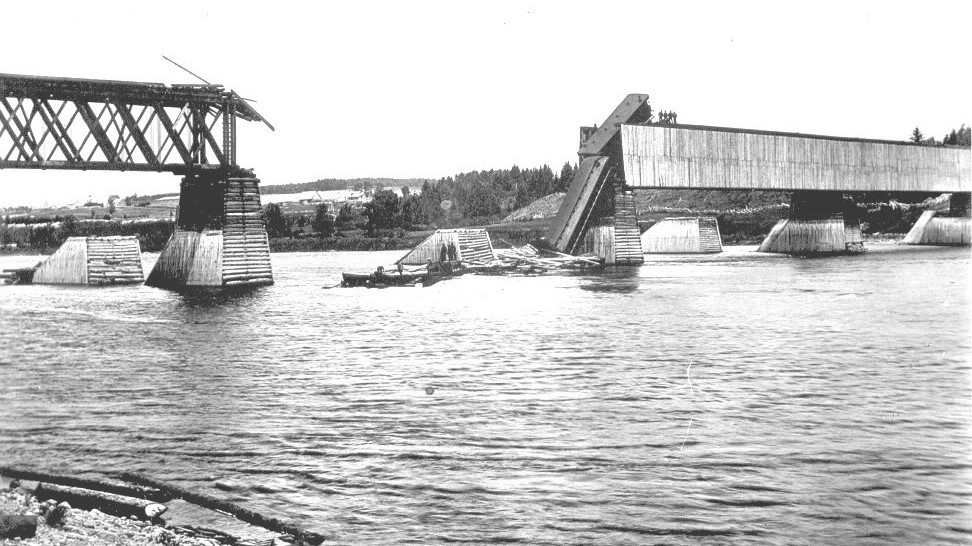 This 120-year-old photograph shows the section of the Grand Falls railway bridge over the St. John River that collapsed, sending CP Rail Locomotive 508 and nine cars into the water on June 21, 1900. A recent span of the river indicates a large metallic mass lies on the riverbed. The piers seen in the background are ice breakers.