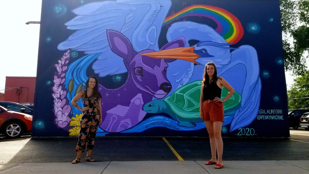 Local artists Penny Heather, left, and Laura Forrester stand in front of the 30-foot mural they painted on the side of S/S Tire & Auto. The project was commissioned by Downtown Fredericton Inc.