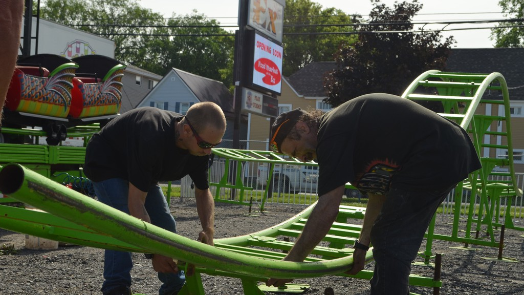 East Coast Amusements employees Cory Thibodeau, left, and Preston Lutz assemble an amusement ride at the Capital Exhibition Grounds on Monday.