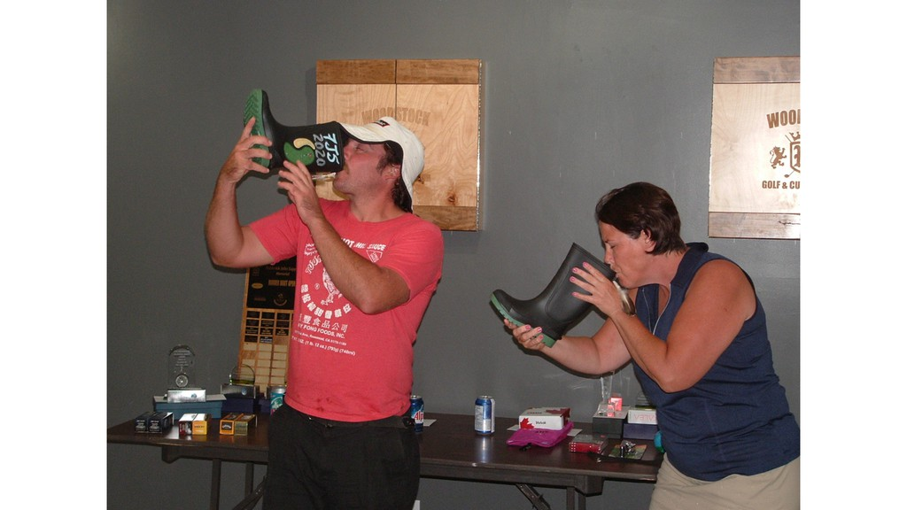 Tim MacLean, left, and Nicki Giberson drink from rubber boots after winning the 24th Frederick J. Sappier Memorial Rubber Boot tournament.