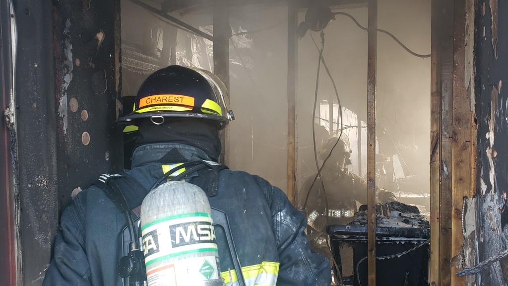A firefighter enters the Pik-Quick convenience store in Campbellton last year. That building fire as well as several others remain unsolved, and the RCMP would like any information the public can provide.