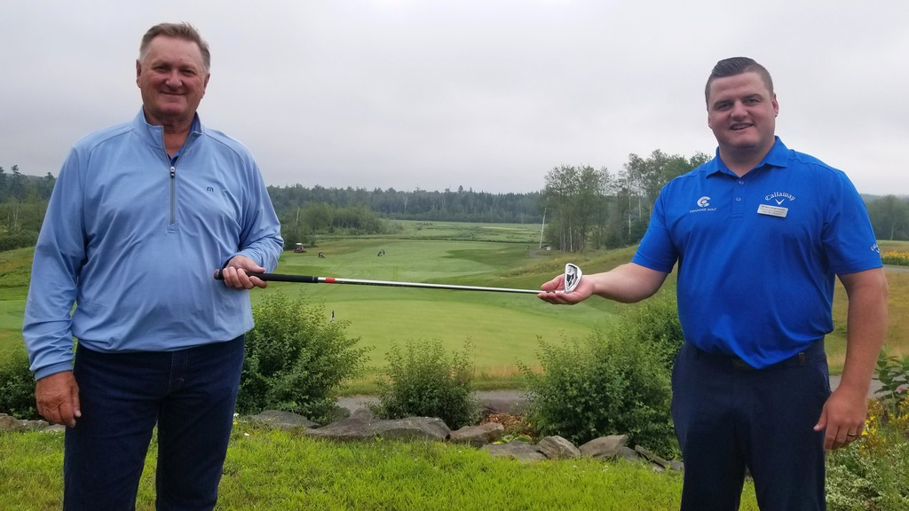 Rick Moser, left, and Kingswood assistant golf pro Andrew Connors hold up the 7 iron Moser used to ace No. 7 at the Fredericton golf course last week. It was his first swing with the club, which he was only using because his Callaway order was destroyed en route from California.