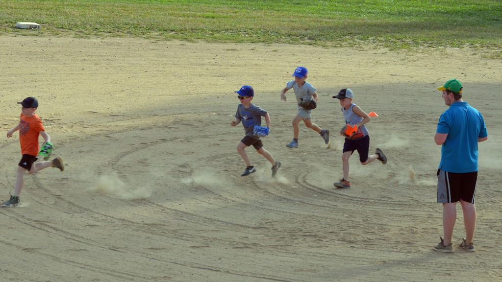 Ball clinic coach Sean Sullivan gets the kids to run around the diamond.