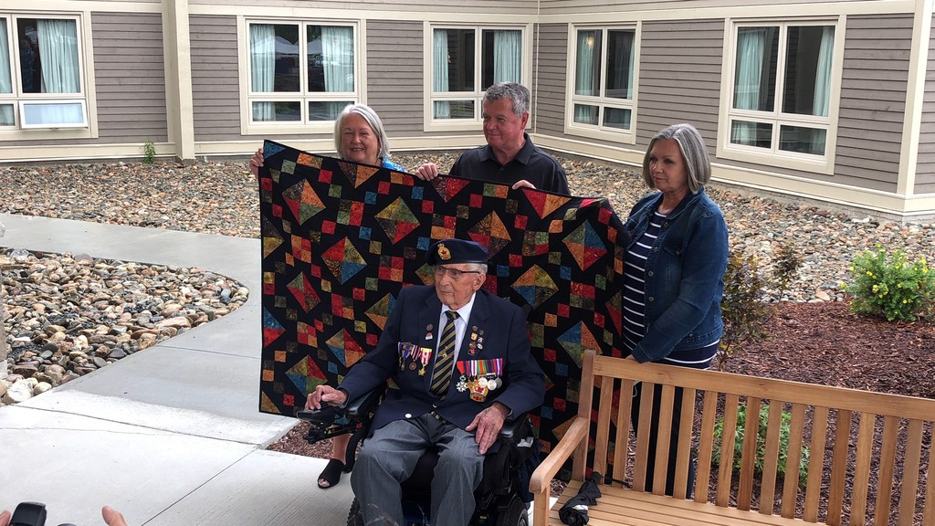 Second World War veteran Cecil Mullin, seated, watches as his daughter Faye, left, son Brad, and daughter Colleen hold up the quilt of valour he received Tuesday at Bridgeview Plaza in Miramichi from Royal Canadian Legion Northwest Miramichi Branch 90 in Sunny Corner.