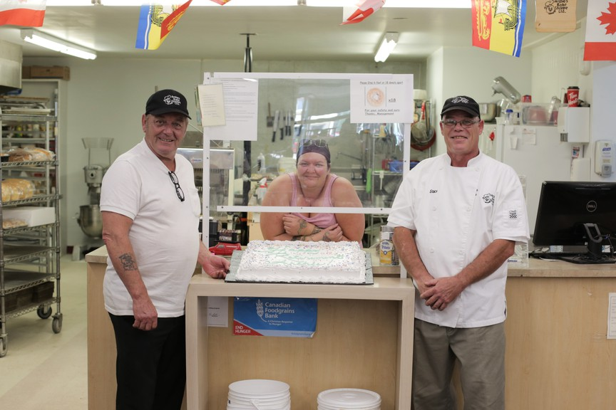 Owner of Archie's Bake Shoppe Archie Dorie, left, his daughter Alysia Smith, who works as a cake decorator, and the new owner, Stacy Haevens, celebrate Dorie's retirement with a big cake on July 31.