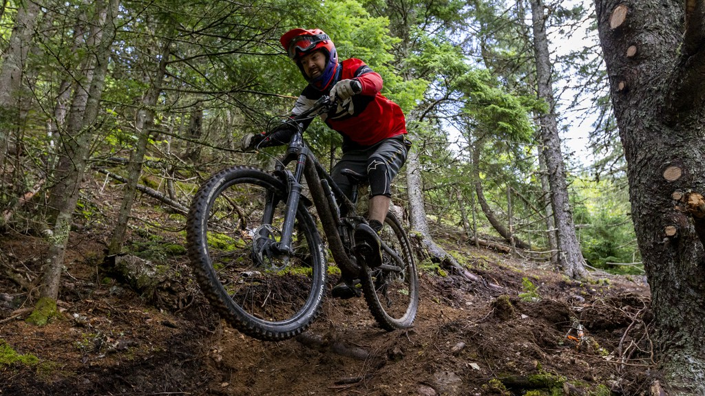 A rider rolls through a Rooty section of trail Saturday during opening day for Poley Mountain's new mountain bike trails. Heavy rains in the morning made for slick, muddy riding.