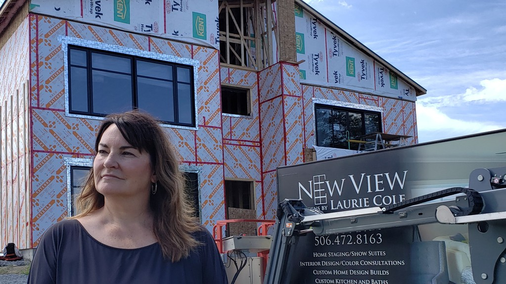Laurie Cole, owner of Fredericton-based New View Design, seen here Sunday in front of a new house she is building in Island View, says the housing market is hot right now, but there has been no big spike in out-of-province buyers.