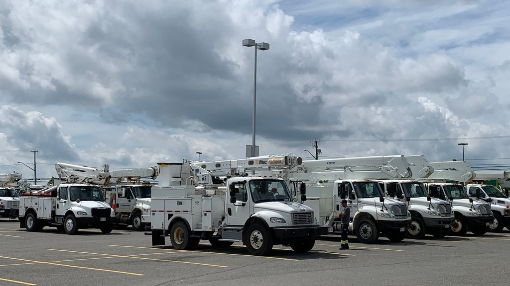 Holland Power Services utility trucks sit in the Connell Mall parking lot in Woodstock on Monday afternoon. New Brunswick utility trucks are now in the United States to clean up downed power lines in the aftermath of Tropical Storm Isaias.