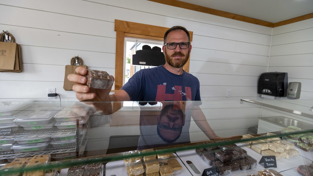 Cobbler's Lane Fudge Factory co-owner Andrew Smith shows off a piece of fudge inside their new location on Marble Street in Sussex Tuesday Aug. 4, 2020. Smith said the first month of business in the new location has far exceeded expectations.