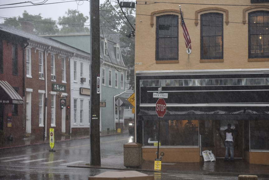 A man takes shelter under an awning as Tropical Storm Isaias inundates the City Dock area of Annapolis, Md., on Tuesday, Aug. 4, 2020.