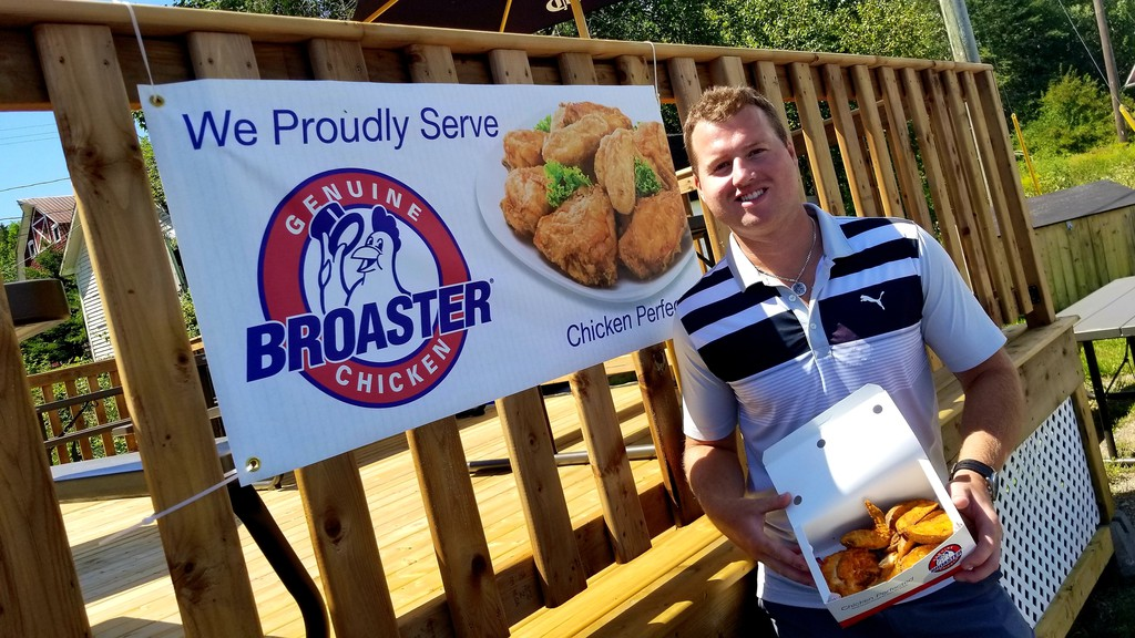Ben Black, owner of the new Railside Cafe in Harvey Station, holds up a three-piece box of Broaster Chicken - the takeout's specialty - and taters.