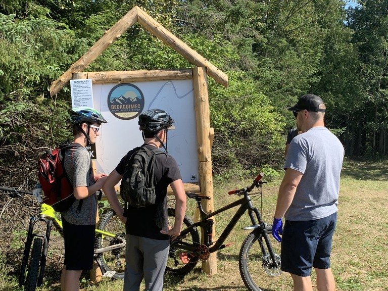 Mountain bikers look over the map of the Becaguimec Trail system. The Becaguimec Trail Association celebrated its new system of bike and walking trails in Hartland on Saturday with a ribbon cutting.
