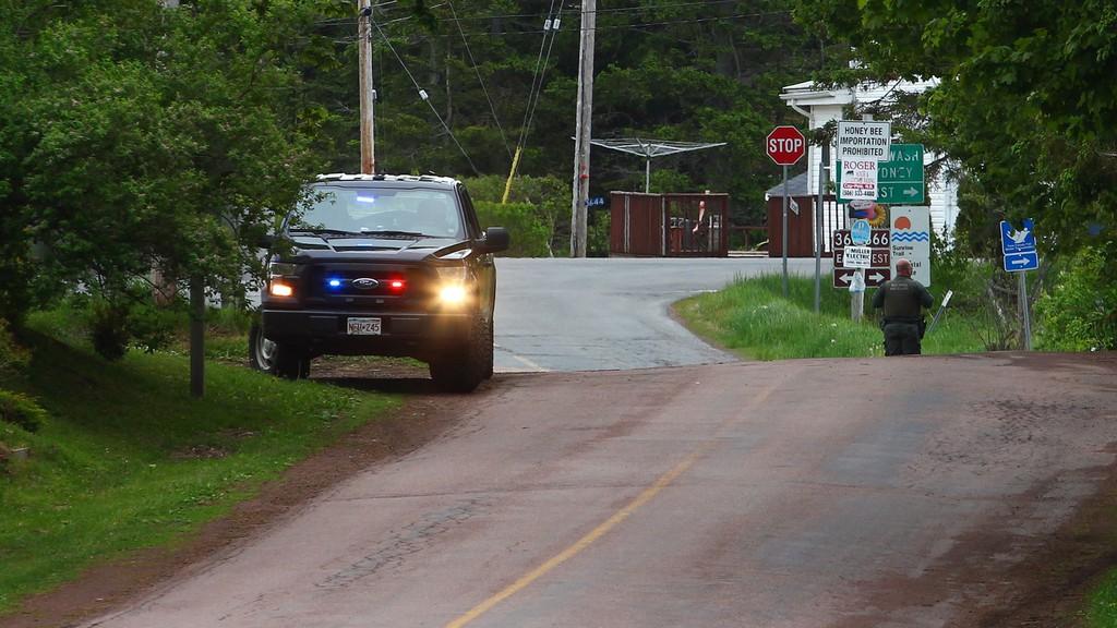 A New Brunswick peace officer monitors the New Brunswick-Nova Scotia border on Tidnish Road, near Baie Verte, N.B., in June.