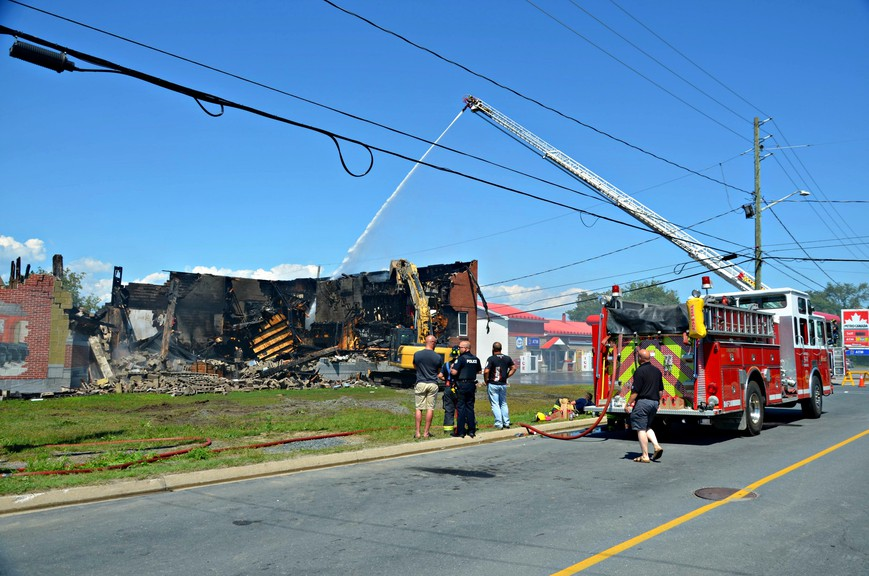 Firefighters from the Miramichi Fire Department spray down the remains of the historic Vogue Theatre Sunday in the former town of Chatham.