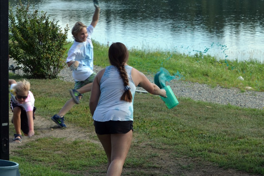 A kid attempts to dodge paint being tossed at him by volunteers during Hartland's colour run.
