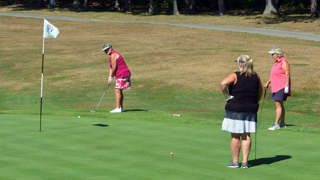 Debbie Tapley and Evelyn Kitchen watch as Loree Kay puts on the green of the final hole during the Woodstock Golf and Curling Club's championship on Sunday.