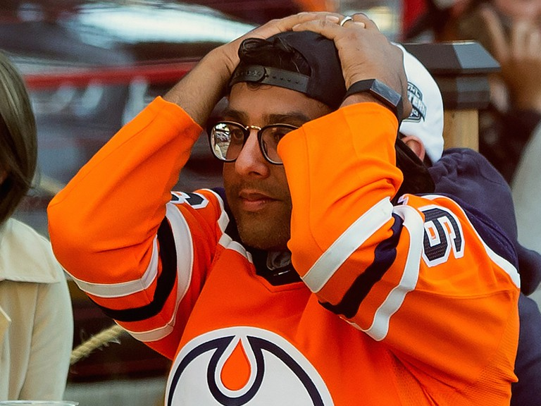 An Edmonton Oilers fan reacts to the team's loss to the Chicago Blackhawks and elimination from NHL playoff contention in downtown Edmonton on Friday, Aug. 7, 2020.