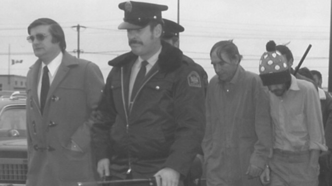 Former Moncton police chief Greg Cohoon, far left, and officer Bud Morin escort James Hutchison and Richard Ambrose (in hat) to a court appearance in 1974. The pair were convicted of murdering two police officers. Ambrose later changed his name to Richard Bergeron and remains in prison. Hutchison died in 2011.