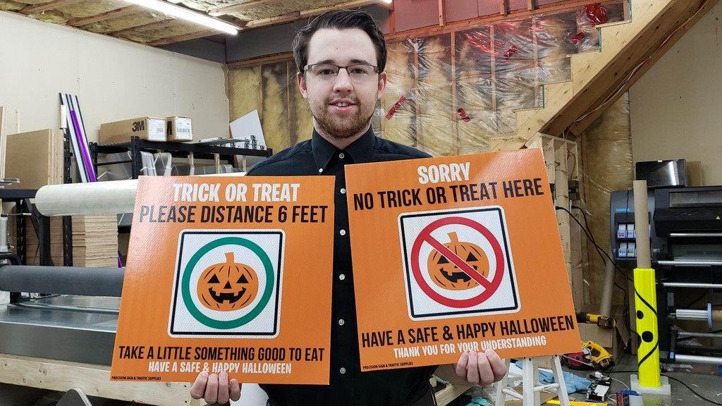 Mike Hay, owner of Precision Sign and Traffic Supples, shows off his COVID-19 Halloween signs in his shop in Lincoln.