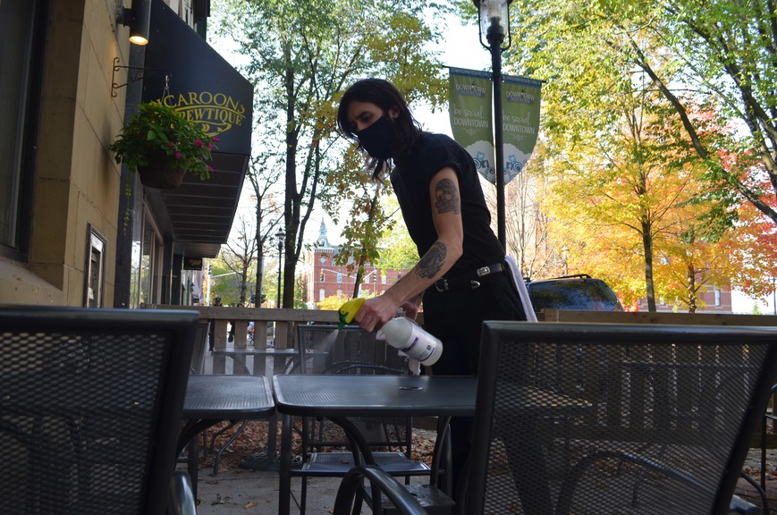 Josh Bravener, employee at Gahan Riverside, cleans a table on the restaurant's patio on Queen Street.