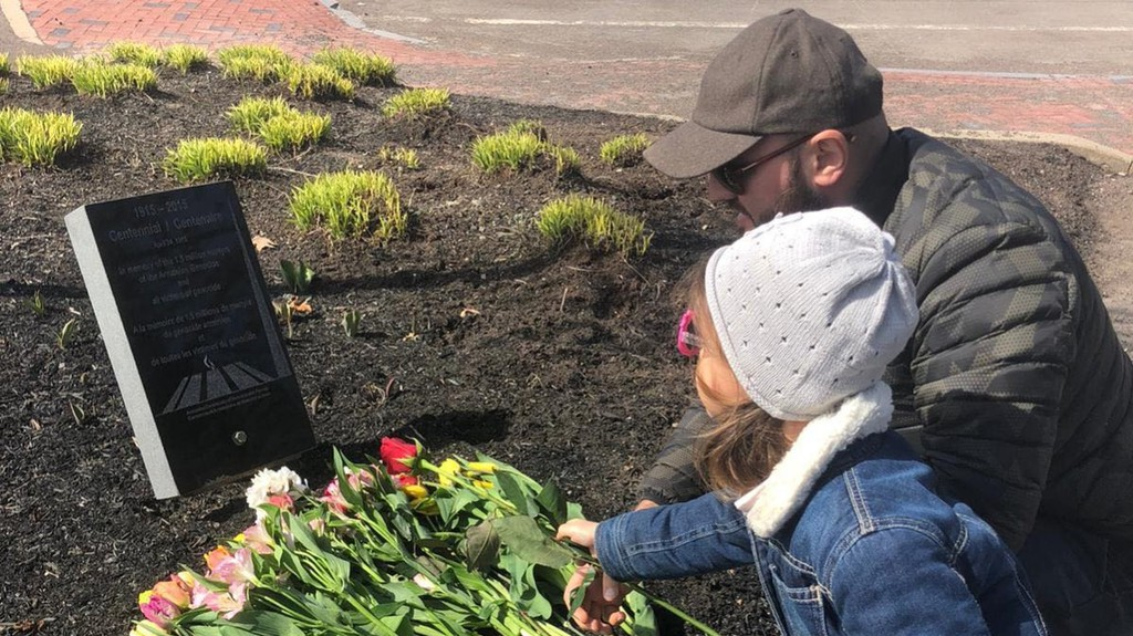 "Andranik Shahbazyan, an Armenian living in Moncton, with his child in front of a memorial for the 1915 genocide in downtown Moncton. Shahbazyan describes watching and reading about the violence affecting Armenians over the last three weeks as ""like a nightmare."" He already knows some of the dead."
