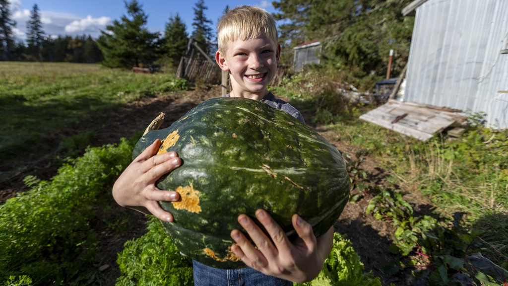 Ben Bannister, 9, shows off the impressively large buttercup squash he grew this year in his grandfather's garden.