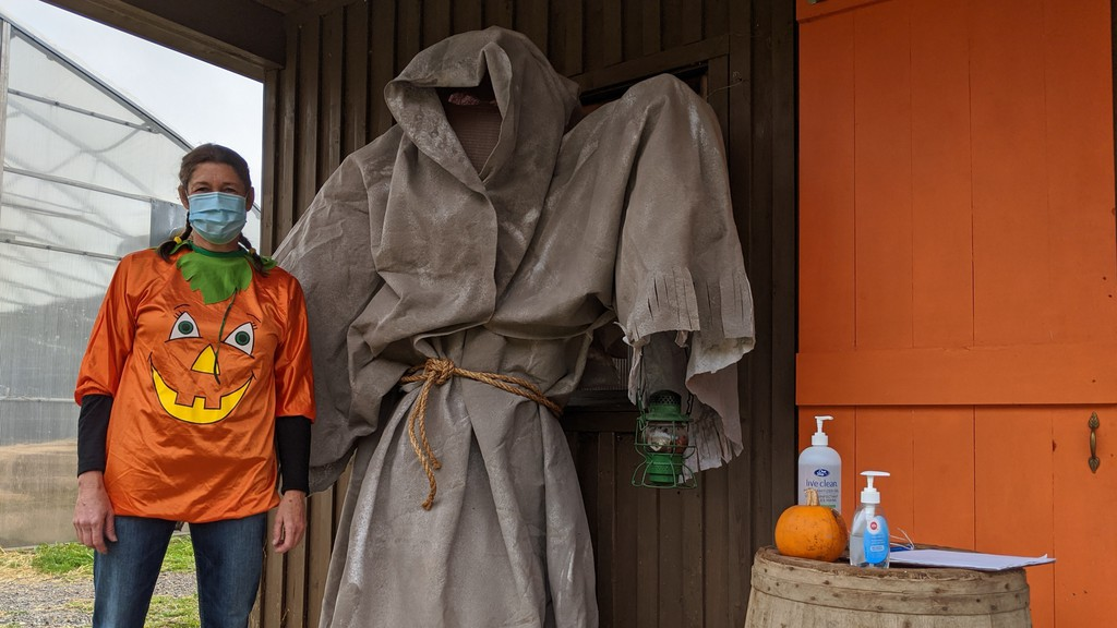 Farmer Brown's Greenhouse co-owner Lisa Brown poses next to the 'Mud Reaper' on Saturday morning. Farmer Brown's Greenhouse will be hosting a Ghosts in the Greenhouse Halloween event the last weekend in October.