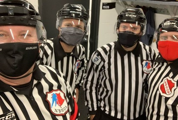 Hockey officials are adjusting to new protocols put in place due to the COVID-19 pandemic. Wearing masks before heading onto the ice for a junior A game in Edmundston are, from left, referee Steve O'Shaughnessy, linesmen Jason Bartlett and Eric Belanger and referee Patrick Dube.