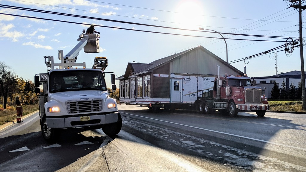 A modular building passes under power and telephone lines at the intersection of Berry Mills Road and Horseman Road Thursday morning. The building was moved to a new location on Price Street, off Elmwood Drive.