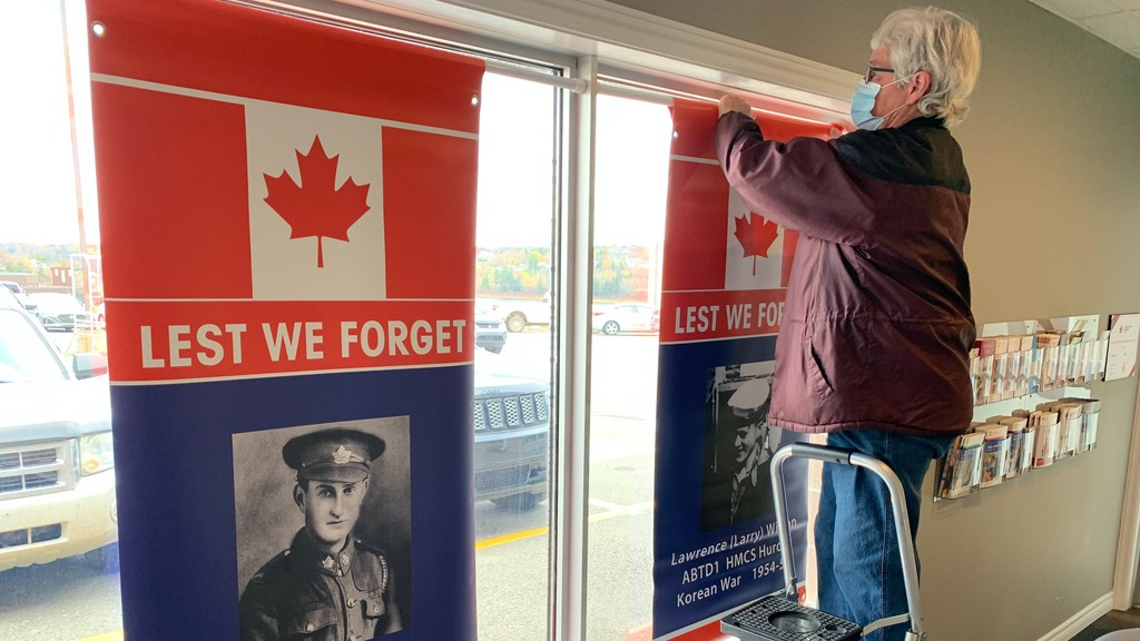 Hartland Legion President Gloria Foster puts up banners of Korean War veteran Lawrence (Larry) Wilson and First World War veteran Pte. Cecil R. Prosser in windows at the office of Dr. Allison Moore in Hartland. Foster has 40 banners going up in the town from now through Remembrance Day.