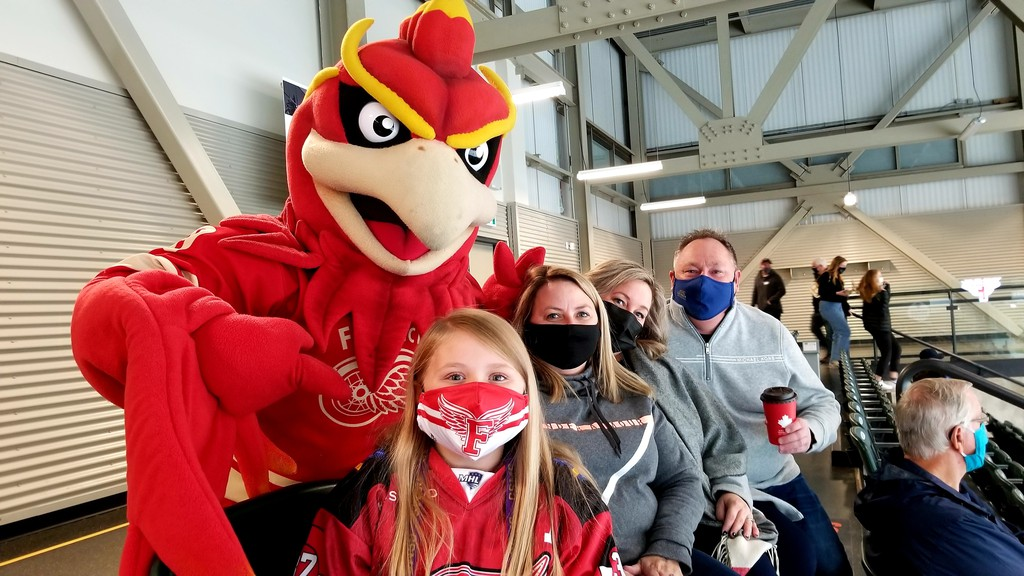 Fredericton Red Wings mascot Wingnut poses for a photo with four of the 517 fans – the maximum allowed due to COVID-19 protocols – at Friday night's Maritime Hockey League game against the Edmundston Blizzard at the Grant-Harvey Centre. From left are Allisha Hare, 10, mom Marsha Hare, Paula Curtis and husband Robert Curtis.