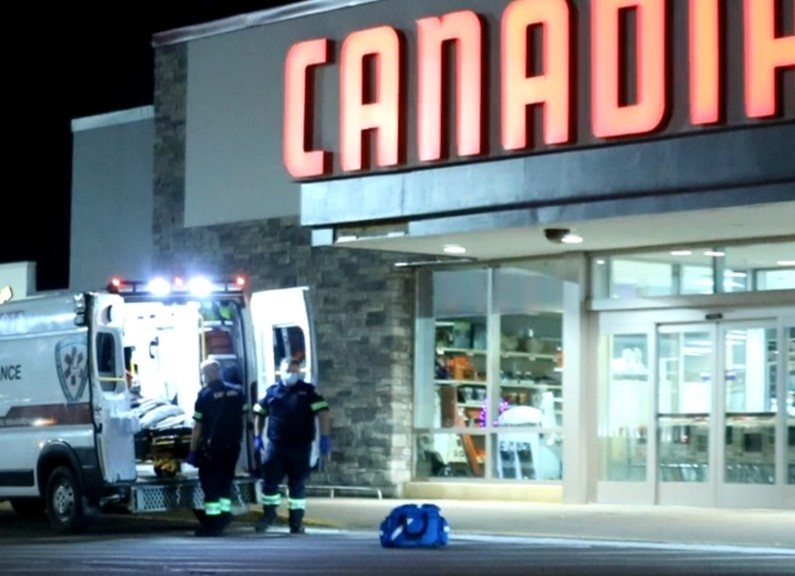 Paramedics aid a person in front of the Canadian Tire on Mountain Road on Saturday evening.