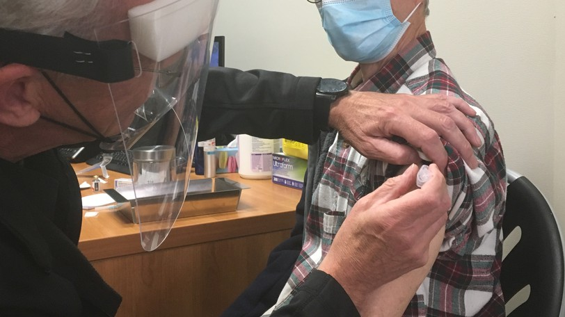 A patient receives a flu shot from a pharmacist.