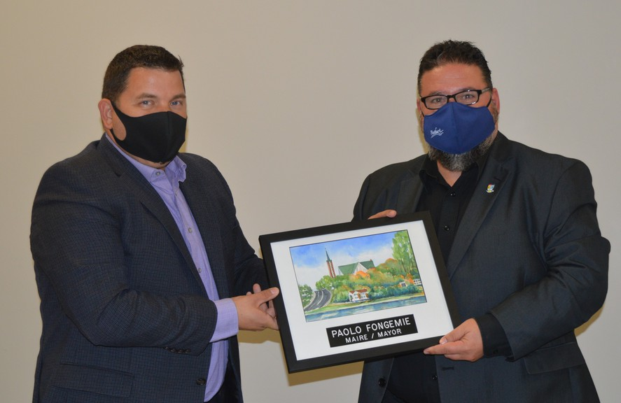 Todd Pettigrew, left, city manager, presents a thank you gift to Paolo Fongemie, who will step down as mayor on Nov. 30. Fongemie has accepted a role as Vice-President of Administrative Services for theCollège communautaire du Nouveau-Brunswick.