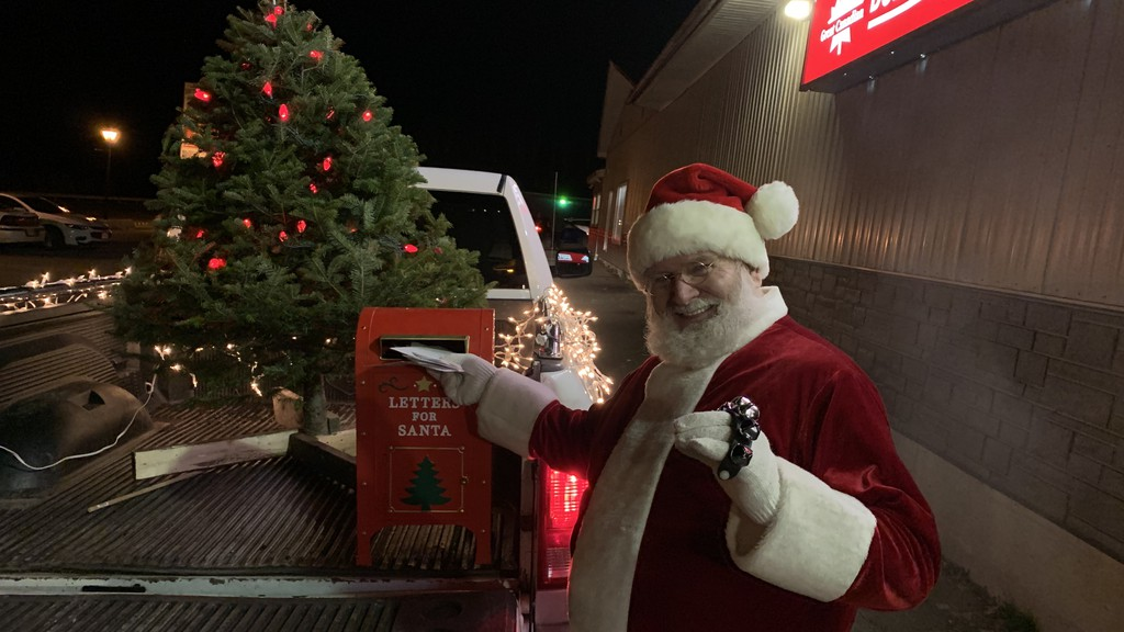 Santa Claus places letters from children into his mailbox while making visits to Florenceville-Bristol businesses on Thursday night.