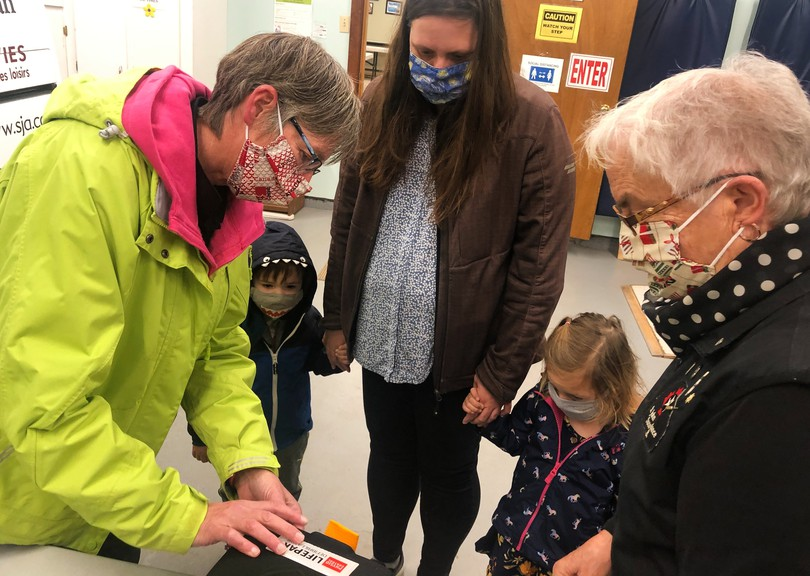 St. John Ambulance volunteer Kimberly Giddens teaches Lisa White about the AED the first aid organization donated to the family from Belleisle on Nov. 23. Her young twins, Henry and Tilly, who were diagnosed with a genetic heart disorder at birth, stand by and watch.