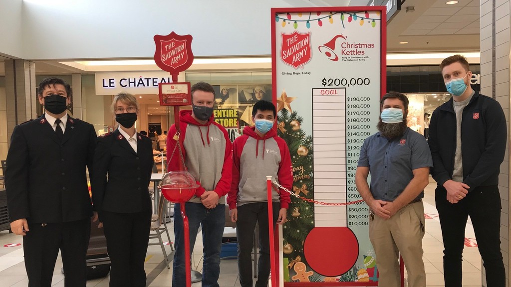 Majors Orest and Tracy Goyak, left, stand with volunteers at the kettle campaign thermometer in McAllister Place Mall.