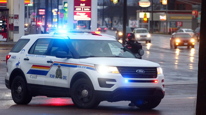 An armed Codiac Regional RCMP officer keeps watch as two people are arrested at a home at the corner of Lorne Street and Oakland Avenue on Dec. 2, 2020.