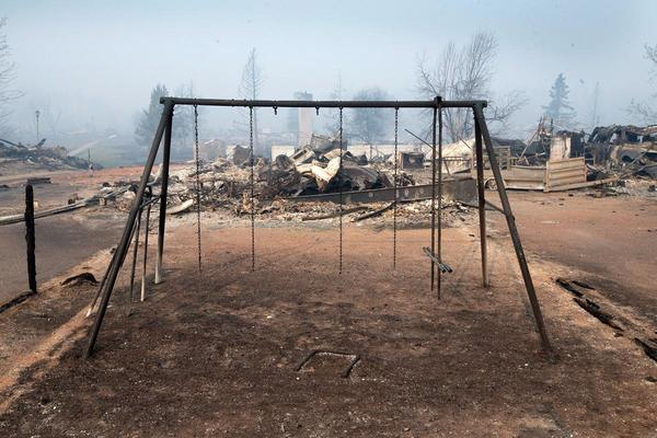 A swing set with the swings burned away sits in a residential neighborhood destroyed by a wildfire on May 6 in Fort McMurray, Alberta, Canada. Wildfires, which are still burning out of control, have forced the evacuation of more than 80,000 residents from the town. (Scott Olson/Getty Images)