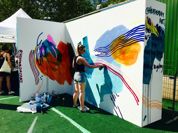 Heather Day, a San Francisco-based artist, painting a mural in real time at the festival.